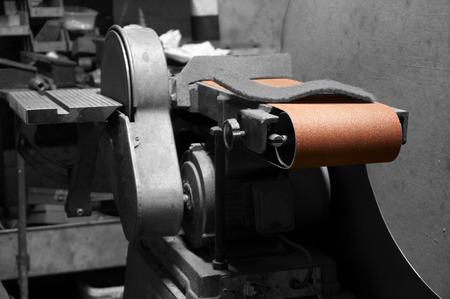 Industrial belt sander in a factory workshop with selective color