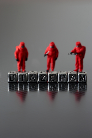 Diazepam on beads with a miniature scale model safety chemicall team Stock Photo