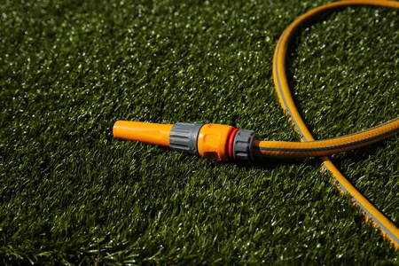 Hose pipe and sprayer attachment lying on grass in sunshine Stok Fotoğraf