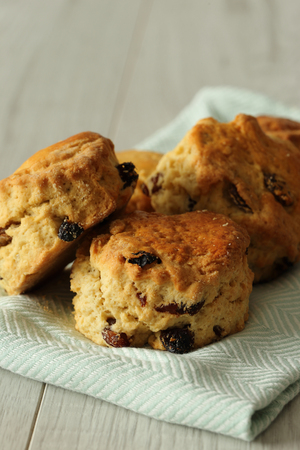 Fruit scones on a pastel green tea towel with a grey wood background