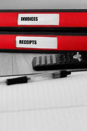 Red folders with invoices and receipts written on the label on a desk with selective colour