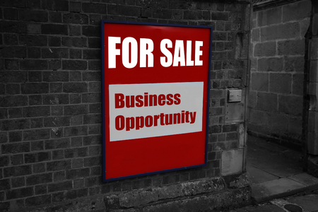 For sale with business opportunity written on a sign attached to a brick wall with selective colour 免版税图像 - 112519179
