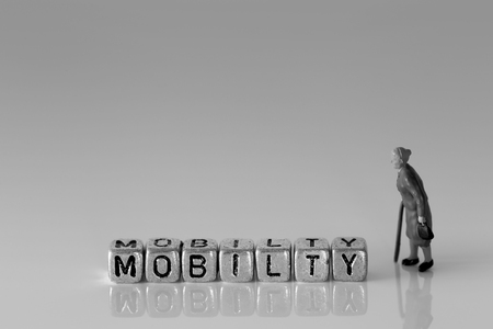 Miniature scale model senior pensioners talking with the word mobility on beads Stock Photo