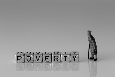 Miniature scale model senior pensioners talking with the word poverty on beads
