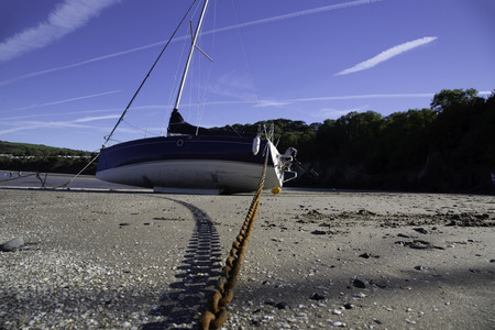 Yacht boat on a sandy beach tethered with a rusty chain on a sunny day with shadows