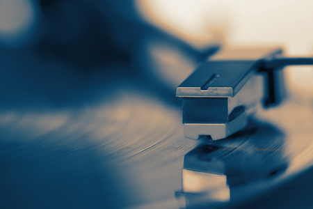 Close-up of a record player playing a vinyl record with colour toning