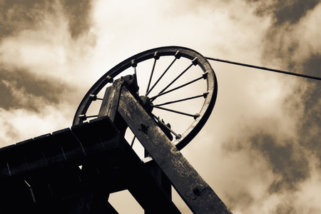 Old Victorian coal shaft tower and wheel pulley with colour toning Standard-Bild
