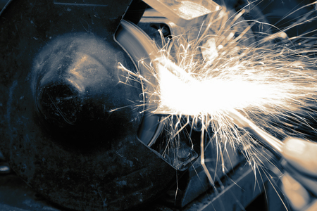 Grinding metal with an electric grinder machine with sparks in a workshop with toning