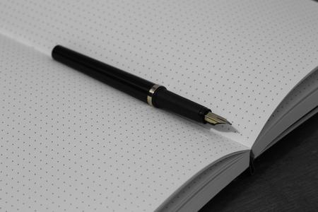 Bullet journal avec des pages blanches et un stylo plume au milieu sur un fond de bois