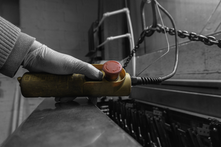 Uomo che aziona un controllo per un paranco per gru da interni in un'officina di fabbrica con colore selettivo