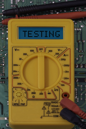 Digital multimeter multitester on a circuit board with the word testing on the display Banque d'images