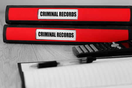 Red folders with criminal records written on the label on a desk with selective colour