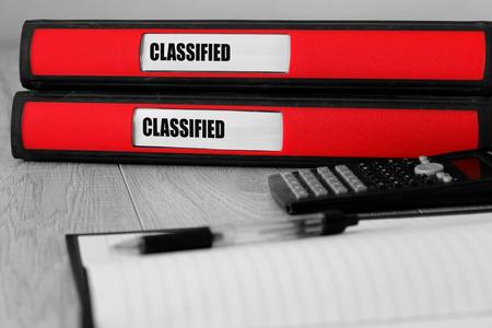 Dossiers rouges avec classé écrit sur l'étiquette sur un bureau avec une couleur sélective Banque d'images