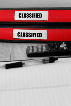 Red folders with classified written on the label on a desk with selective colour