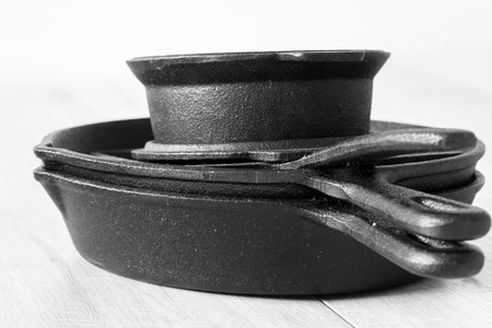 Set of  black cast iron pots and pans on a grey wood background Imagens