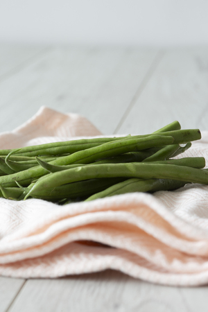 Green beans organic and freshly picked drying on a pink tea towel with grey wood background