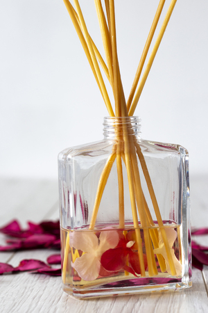 Reed diffuser with fragrance in a glass jar with rose petals on a grey wood background
