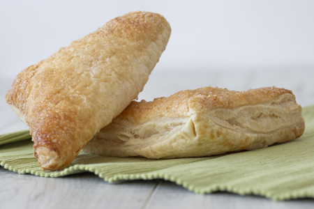 Apple turnover on a green tea towel with a grey wood background