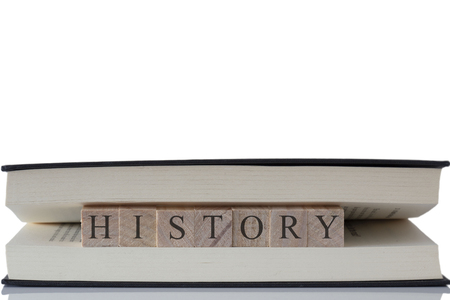 History written on wooden blocks inside a book isolated on a white background with reflection