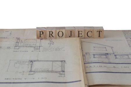 Project written on wooden blocks on house extension building plans blueprints with a white background