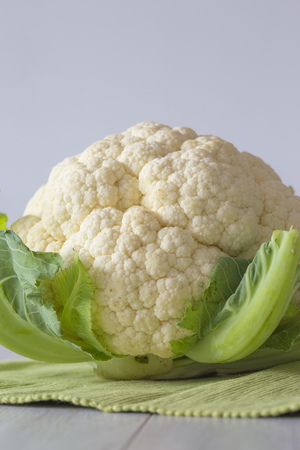 Cauliflower with leaves on a green tea towel with a grey wood background