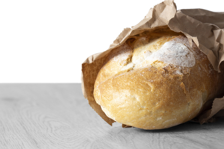 Loaf of white bread in a brown paper bag on grey wood.  Recycle packaging concept.  No plastic waste.