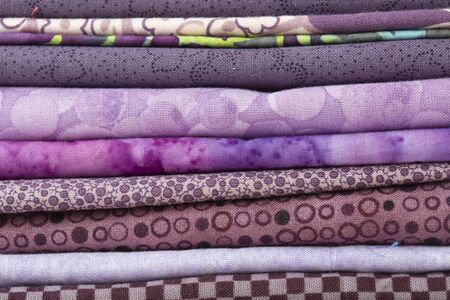 Various fabric material sample swatches,  with a purple theme, stacked on top of each other