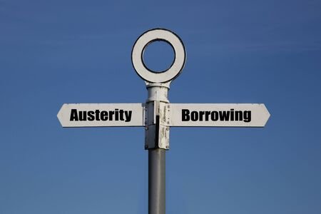 Old road sign with a choice between austerity and borrowing written on it. Government fiscal policy concept
