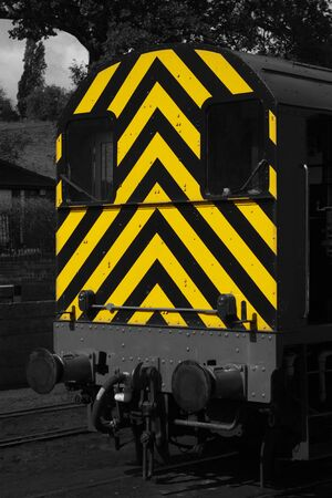 Diesel freight train locomotive with yellow and black warning hazard safety diagonal stripes painted on.  Selective colour abstract image. Stock fotó