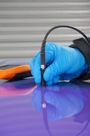 Person using probe, with digital tester, to measure the paint thickness microns on a painted metal panel. Person wearing protective gloves.