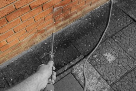 Man pressure washing brick wall with a power wand.  Home maintenance concept with selective colour