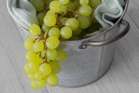 Bunch of white seedless grapes on a green tea towel  in a metal bucket container.  Grey wood background