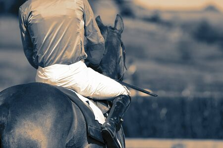Horse racing jockey riding a horse preparing for the start of a race. With colour toning