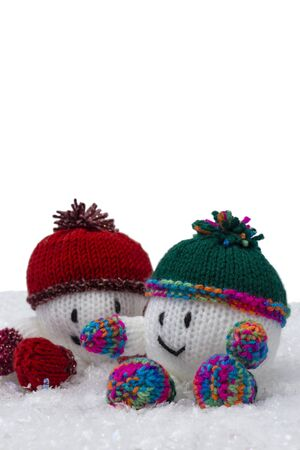 Snowballs knitted Christmas decorations with hat and scarf on artificial snow. With a white background
