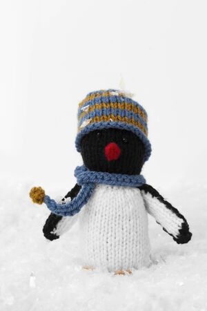 Penguin knitted toy Christmas decoration with hat and scarf on artificial snow. With a white background