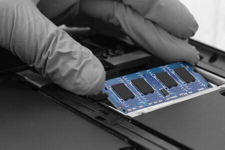 Tecnico che installa la RAM nello slot di memoria su un computer portatile. Immagine astratta con colore selettivo Archivio Fotografico