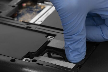 Technician connecting hard drive HDD cable to a laptop computer.  Computer updrade concept