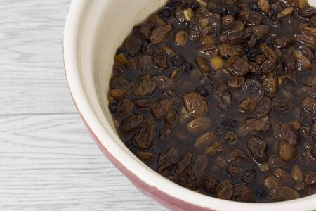 Mixed dried fruit soaking in a tea marinade in a mixing bowl. Grey wood background