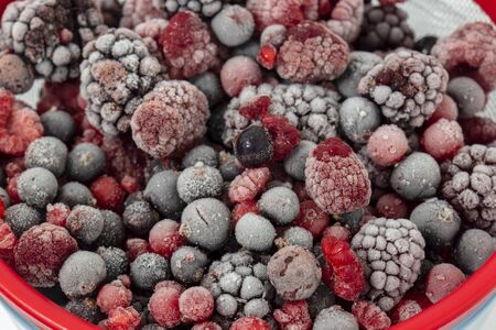 Frozen fruit including red berry, blackberry, blackcurrant and raspberry in a sieve strainer on a white background