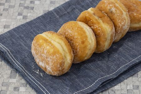 Jam doughnuts coated in icing sugar on a blue tea towel on a kitchen worktop. Mosaic tile background