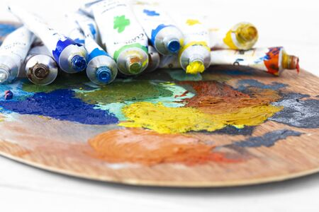 Artists oil paint tubes open and used on a wooden palette,  with mixed colours.  Art and craft supplies concept