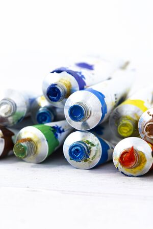 Artist oil paint tubes in various colours on white wood.  Art and craft supplies concept