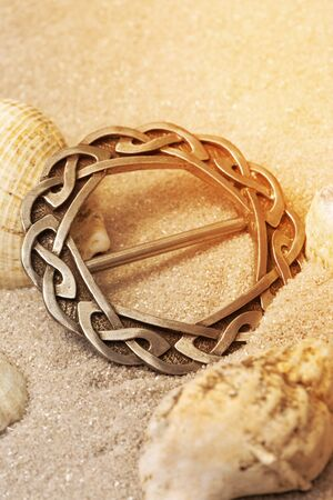 Silver antique old Celtic scarf ring with traditional design border in sand..  Hand made traditional jewellery concept