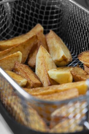 Chips cooking in vegetable oil in a deep fat fryer appliance.  Unhealthy fast food concept with a narrow depth of field 写真素材