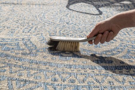 Man brushing an outdoor rug in a garden with a hand brush.  Grey and blue design