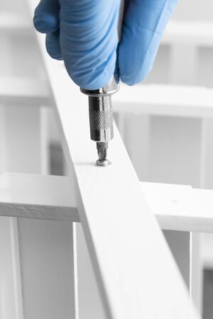 Man assembling a white flat pack ladder shelving unit with a screwdriver.  Flat pack assembly concept