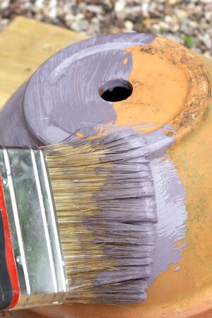 Person painting a terracotta flower plant pot purple,  with a paint brush.  Restoration upcycle concept