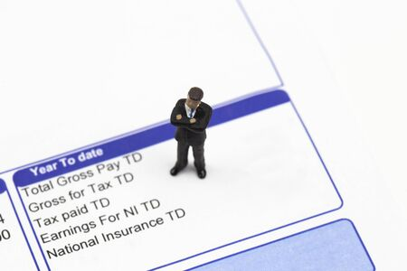 Miniature scale model businessman standing on a wage pay slip showing earnings deductions.  Isolated on a white background 写真素材