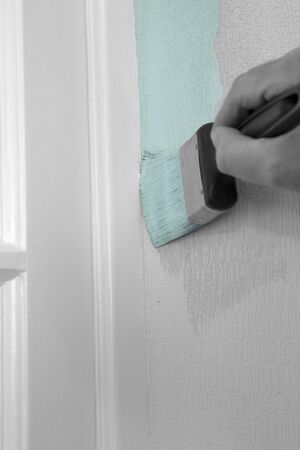 Man painting wall with mint green paint on textured wallpaper,  cutting in against door frame.  With selective colour