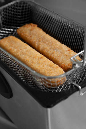 Fish fingers in a mesh basket,  cooked in an electric deep fat fryer appliance.  Fast food concept